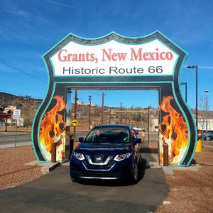 Roguetrippers drive their Nissan Rogue through a giant Route 66 sign
