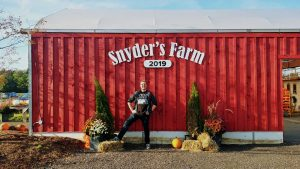 Nick Kulnies of Roguetrippers Poses in front of the Snyder's Farm Sign Every Year we visit.